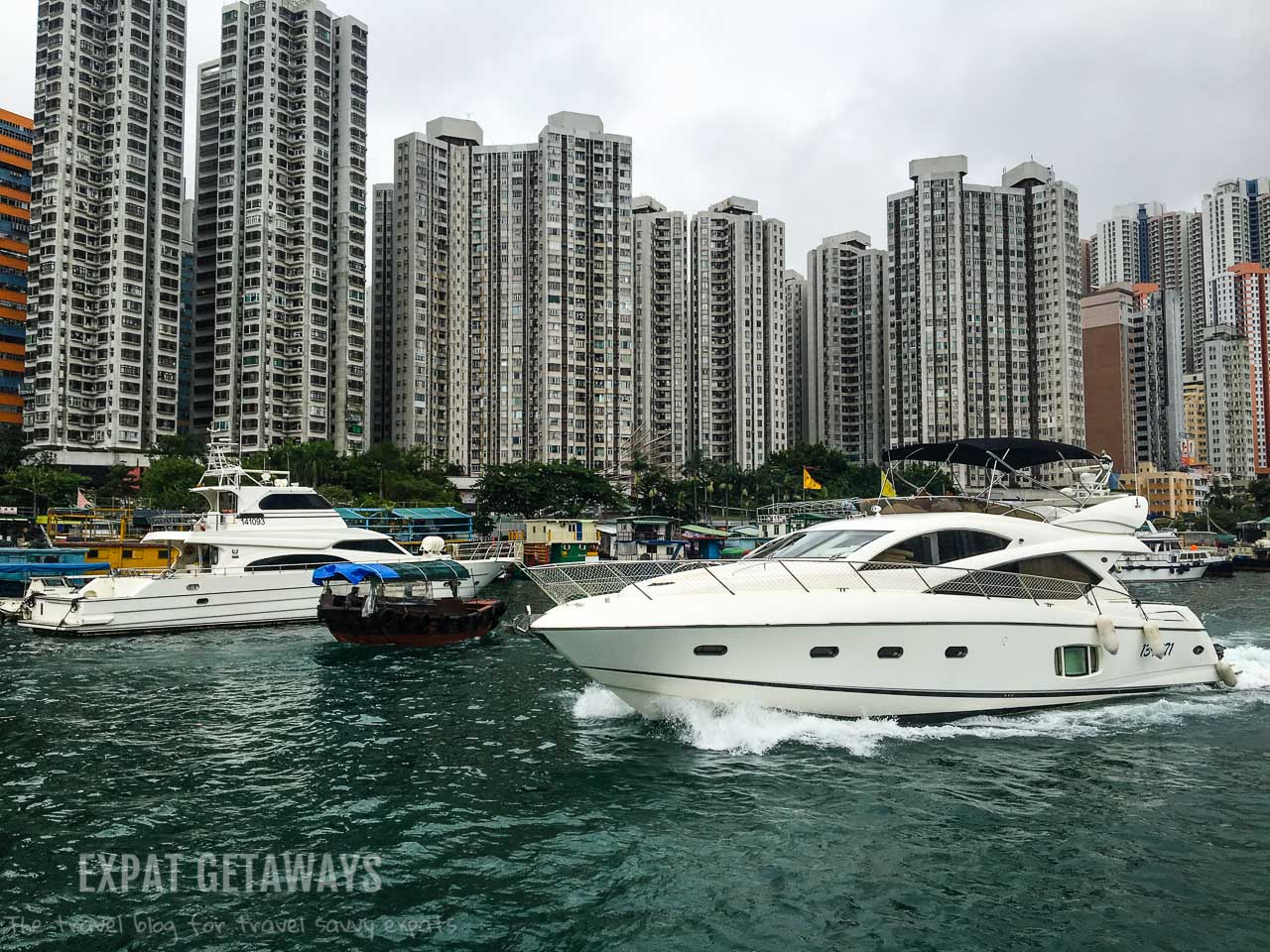 A sampan slips past a luxury yacht. Only in Hong Kong...
